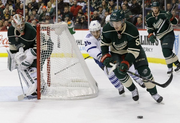 Minnesota Wild center Tyler Graovac (53) controls the puck in front of Toronto Maple Leafs center Mike Santorelli (25) as Wild goalie Darcy Kuemper, l