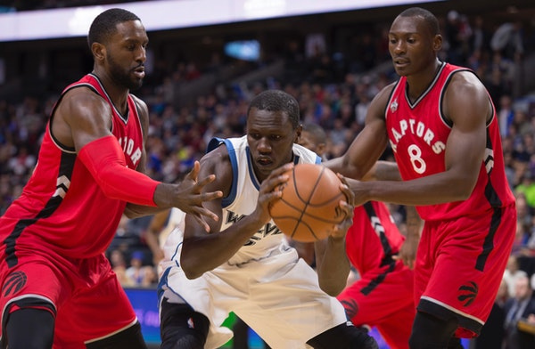 Timberwolves center Gorgui Dieng held the ball under pressure from Raptors forwards Bismack Biyombo, right, and Patrick Patterson during the first hal