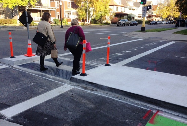 Two women crossed E. 28th Street at Chicago Avenue S. through a pedestrian median designed to make it easier for people to cross.