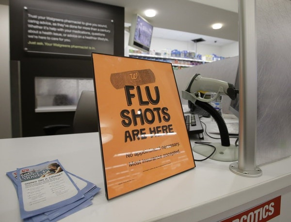 A sign lets customers know they can get a flu shot in a Walgreen store.