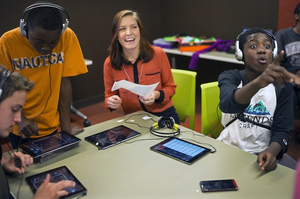 AmeriCorps mentor Jana Greenslit, center, chatted with Ben Leach, 13; Nasir Jackson, 13, and Amier Day, 12, as they created tunes in GarageBand at the