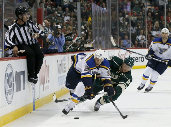 St. Louis Blues center Kyle Brodziak (28) and Minnesota Wild center Mikko Koivu (9), of Finland, fall as they battle for the puck during the second pe