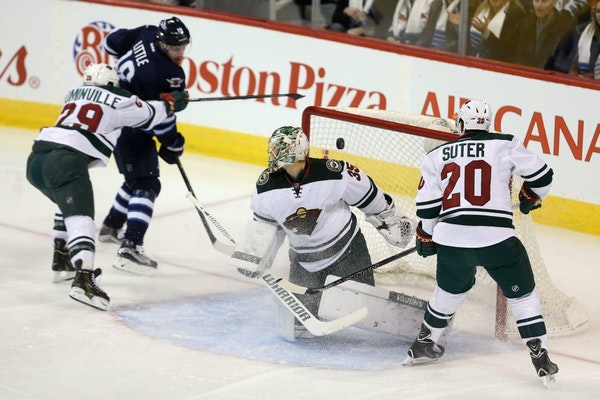 Winnipeg Jets' Bryan Little (18) scores against Minnesota Wild goaltender Darcy Kuemper (35) as he is checked by Jason Pominville (29) with Ryan Suter