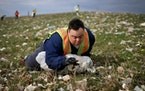 """Scott Rhude, 33, sits spread-eagled in a field of garbage, reaching for a piece of trash while on a work assignment with a sheltered workshop """"enclave"""