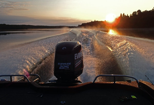 As the sun rose over the treetops lining Lake of the Woods, a boat carrying anglers to favorite fishing spots carved a picturesque wake.