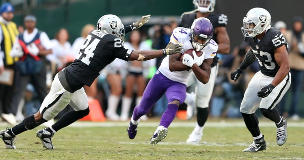 Vikings wide receiver Stefon Diggs split Raiders defenders Charles Woodson (24) and Malcolm Smith (53), picking up a first down in the forth quarter a
