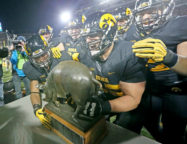 """""""Floyd of Rosedale"""" made it back into the hands of Iowa players after they defeated Minnesota 40-35 at Kinnick Stadium, Saturday, November 14, 2015 in"""