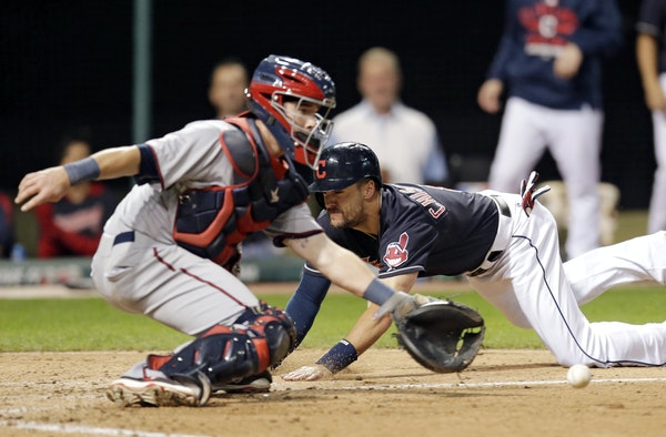 Cleveland's Lonnie Chisenhall slid home safely on Adam Moore's third-inning single in Game 2 as Twins catcher Chris Herrmann fielded the throw.