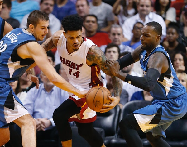 Timberwolves forward Nemanja Bjelica, left, and forward Shabazz Muhammad stripped the ball from Heat guard Gerald Green during the first half Tuesday.