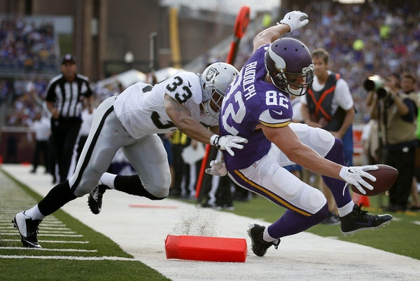 Minnesota Vikings Kyle Rudolph (82) was pushed out of bounds by Tyvon Branch (33) just short of the goal line in the first quarter of an exhibition ga