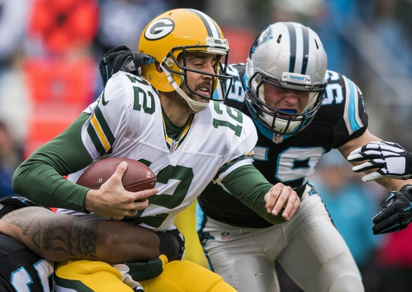 Quarterback Aaron Rodgers felt the heat from Panthers defensive tackle Star Lotulelei, bottom, and linebacker Luke Kuechly during the Packers' secon