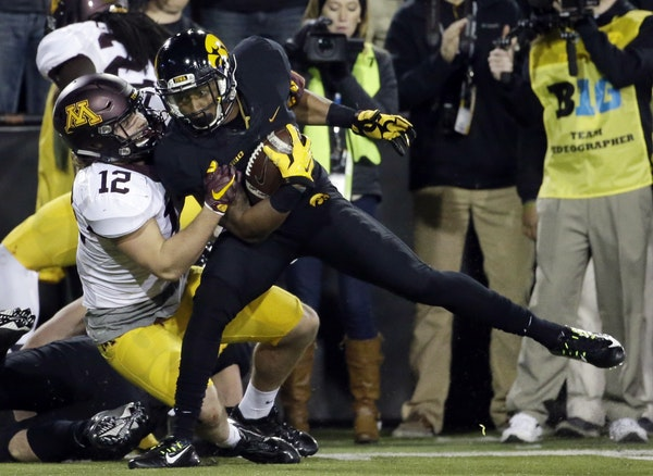 Minnesota linebacker Cody Poock, left, tackles Iowa wide receiver Tevaun Smith during the second half. The catch was part of a 506-yard offensive outp