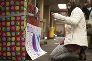 Gracie Tilney-Kaemmer, 12, taped a sign on a box she decorated for toy donations at the International Institute of Minnesota in St. Paul on Tuesday.