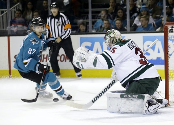 Minnesota Wild goalie Darcy Kuemper, right, blocks a shot next to San Jose Sharks' Joonas Donskoi (27) during the first period of an NHL hockey game S