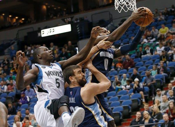 Memphis Grizzlies forward JaMychal Green (0) pulls down a rebound over Minnesota Timberwolves center Gorgui Dieng (5) and Grizzlies center Marc Gasol,