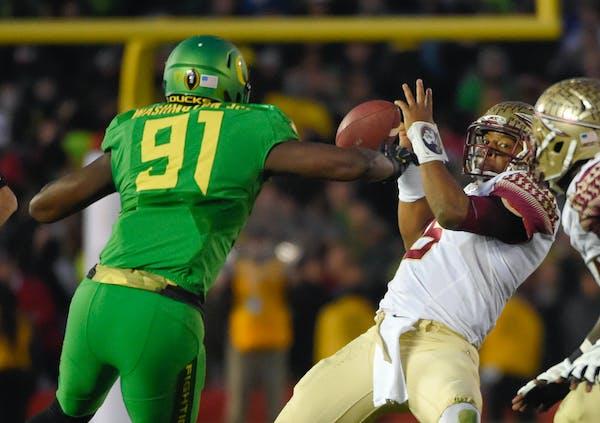 Oregon linebacker Tony Washington, left, knocks the ball away from Florida State quarterback Jameis Winston, right, before going on to score during th