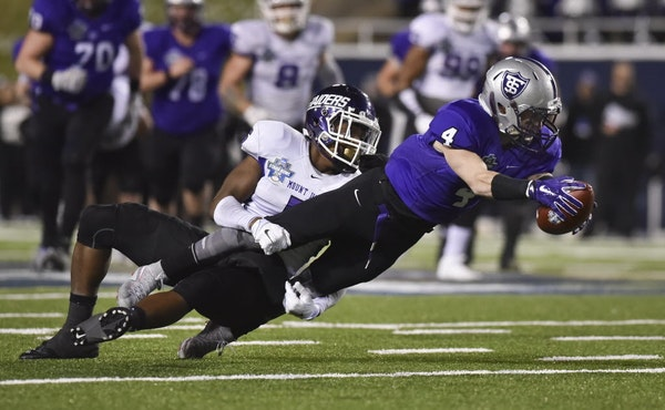 St. Thomas wide receiver Jack Gilliland (4) is tackled after his reception by Mount Union defensive back Tre Jones during the first half of the the NC