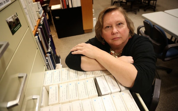 Kathy Klehr, executive director of the Scott County Historical Society, with part of the group's newspaper collection.