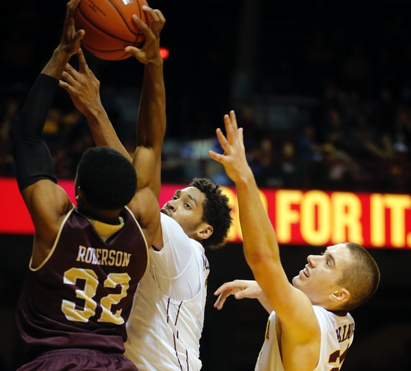 Justin Roberson(32) of Louisiana Monroe goes up for a shot as Jordan Murphy (3) and Joey King (24) of the Gophers defend.