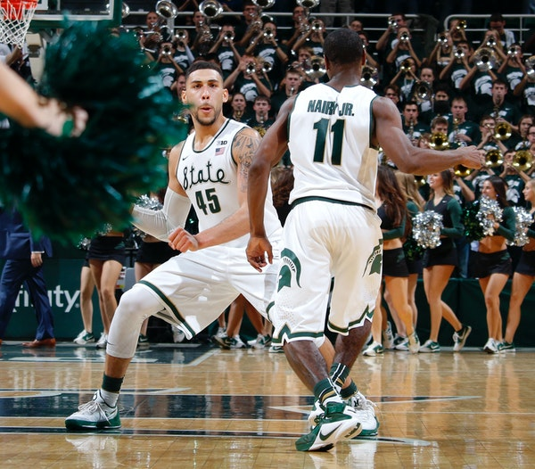 Michigan State's Denzel Valentine (45) and Lourawls Nairn Jr. (11) celebrate following a 71-67 win over Louisville in an NCAA college basketball game,