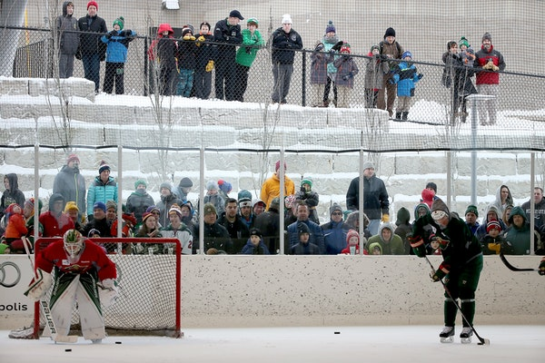 Fans watch as the Minnesota Wild practice at the Backyard outdoor ice rink at Braemar Arena, Tuesday, Dec. 29, 2015 in Edina.