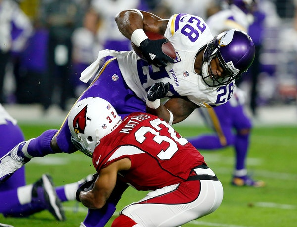 Minnesota Vikings running back Adrian Peterson (28) is hit by Arizona Cardinals free safety Tyrann Mathieu (32) during the first half of an NFL footba