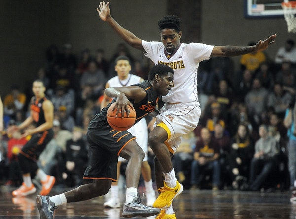 Oklahoma State's Jawun Evans dribbles the ball up the court while Minnesota's Kevin Dorsey guards at the Sanford Pentagon in Sioux Falls on Saturday,