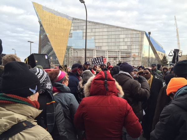 Protesters stopped Saturday outside the Juvenile Detention Center with the Vikings stadium as a backdrop in downtown Minneapolis.