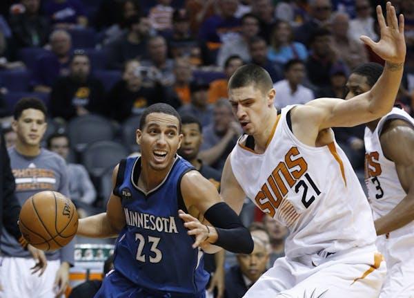 Minnesota Timberwolves' Kevin Martin (23) drives past Phoenix Suns' Alex Len (21), of Ukraine, during the second half of an NBA basketball game Sunday