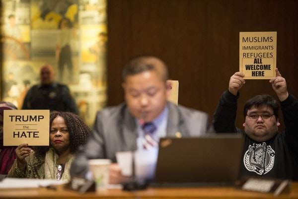 Demonstrators held anti-Trump signs at Wednesday's St. Paul City Council meeting.