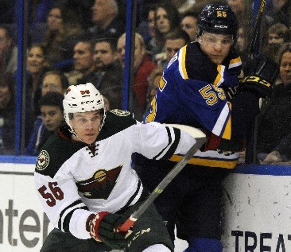 The Blues' Colton Parayko is checked by the Wild's Erik Haula during the first period Thursday.
