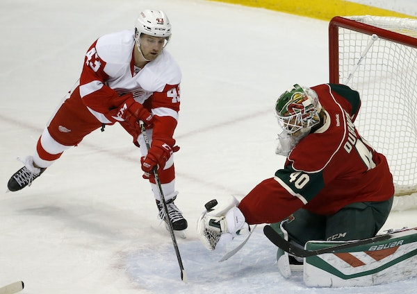 Wild goalie Devan Dubnyk scooped up a shot by Red Wings center Darren Helm (43) during the first period Monday night.