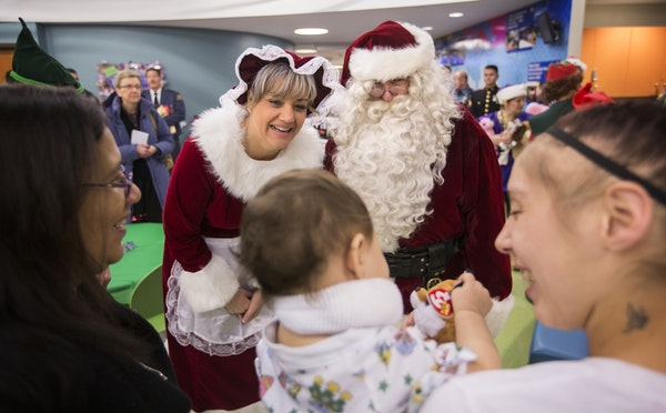 Santa Claus, played by retired St. Paul police officer Tim Bradley, and Mrs. Claus, played by St. Paul police officer Amy Rahlf, visit with nine-month
