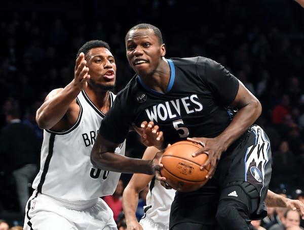 Minnesota Timberwolves center Gorgui Dieng (5) drives the ball around Brooklyn Nets forward Thaddeus Young (30) during the first half of an NBA basket
