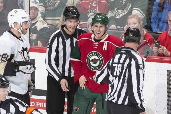 Minnesota Wild left wing Zach Parise (11) laughed with officials after the puck disappeared into his jersey, temporarily haulting a Wild power play la