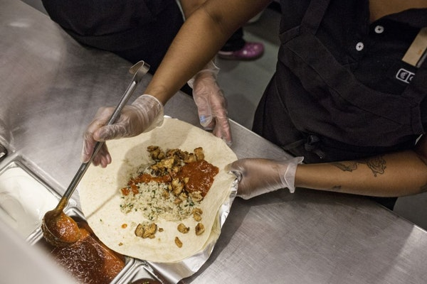 Employees prepare orders at a Chipotle restaurant in New York, April 23, 2015.