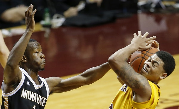 Nate Mason (2) was defended by Jordan Johnson (1) in the first half Wednesday night at Williams Arena.