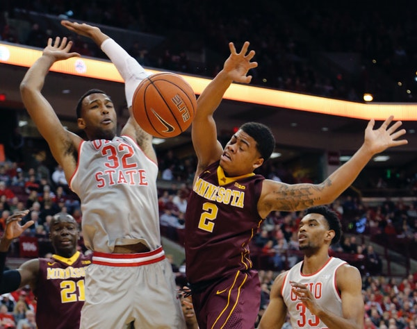Minnesota's Nate Mason, right, loses control of the ball while driving to the basket against Ohio State's Trevor Thompson during the first half of an