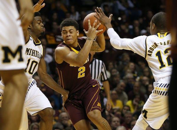 Minnesota guard Nate Mason (2) splits the defense of Michigan guard Derrick Walton Jr. (10) and Michigan guard Muhammad-Ali Abdur-Rahkman (12) during