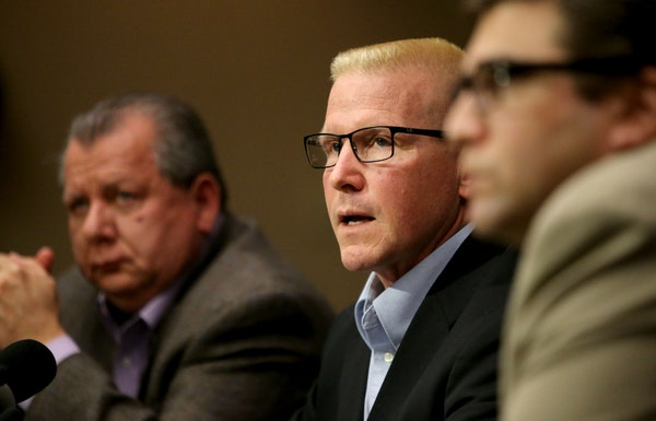 St. Paul Central High teacher John Ekblad, center, speaks to reporters last month at his attorneys' Bloomington office, recounting the injuries and wh
