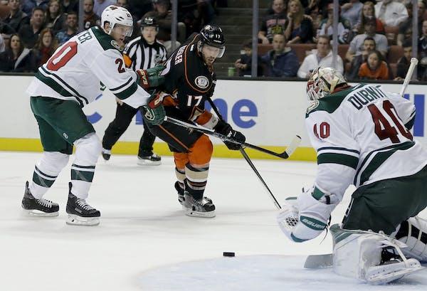 Anaheim Ducks center Ryan Kesler, middle, shoots between Minnesota Wild goalie Devan Dubnyk, right, and defenseman Ryan Suter during the second period