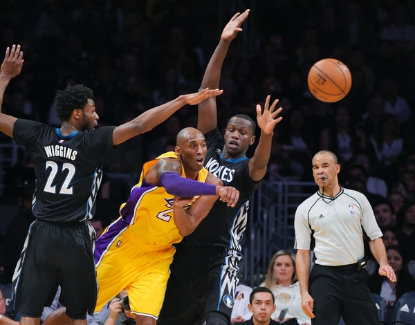 Los Angeles Lakers forward Kobe Bryant, second from left, passes the ball as Minnesota Timberwolves guard Andrew Wiggins, left, and center Gorgui Dien