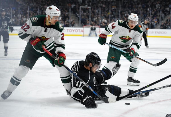 Los Angeles Kings center Anze Kopitar, center, of Slovenia, falls as he vies for the puck with Minnesota Wild right wing Nino Niederreiter, left, of S