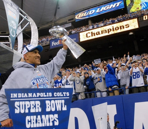 FILE - In this Feb. 5, 2007, file photo, Indianapolis Colts coach Tony Dungy shows the Vince Lombardi Trophy to fans while riding a float in the RCA D