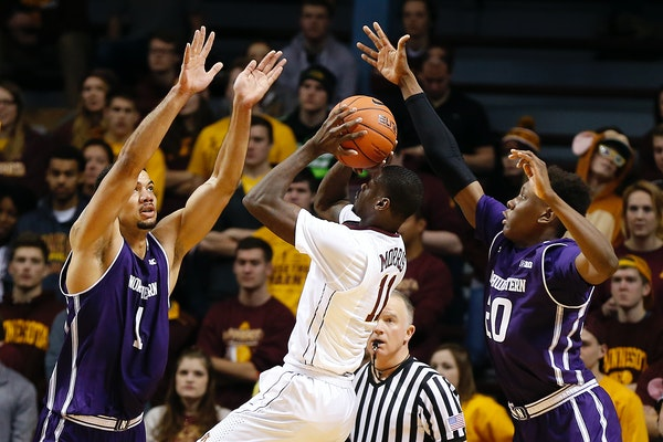 Gophers senior Carlos Morris (11) shot the ball as Northwestern center Joey van Zegeren (1) and guard Scottie Lindsey defended in the first half Satur
