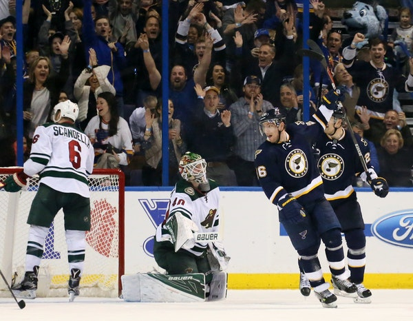 St. Louis Blues center Paul Stastny, second from right, reacts after scoring an unassisted goal past Minnesota Wild goaltender Devan Dubnyk during the