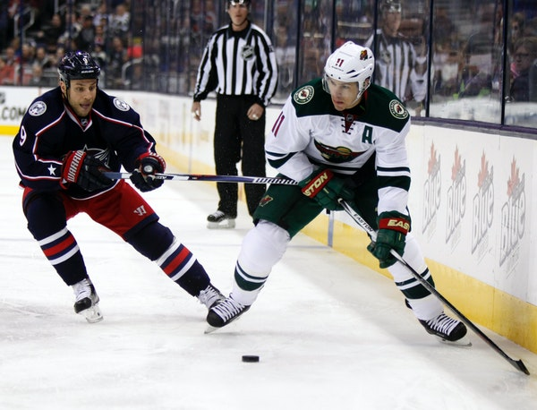 Minnesota Wild's Zach Parise, right, works for the puck against Columbus Blue Jackets' Gregory Campbell during the first period of an NHL hockey game