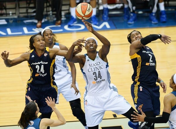 Lynx center Sylvia Fowles (34) grabbed for a loose ball while being challenged by Indiana forwards Tamika Catchings, left, and forward Erlana Larkins