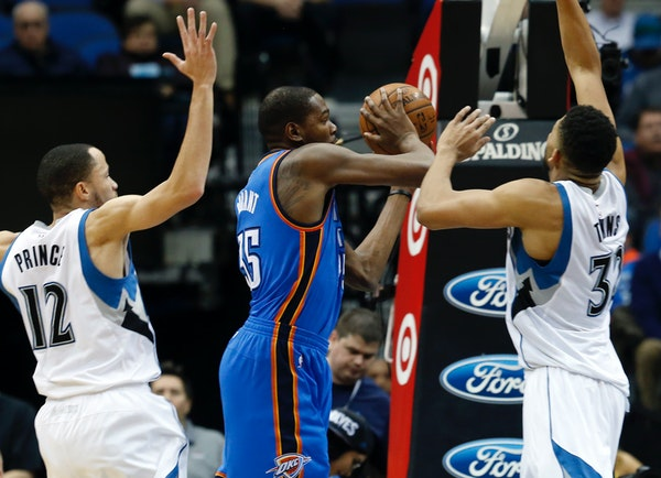 Oklahoma City's Kevin Durant looked to pass between the Timberwolves' Tayshaun Prince, left, and Karl-Anthony Towns in the first quarter during a game