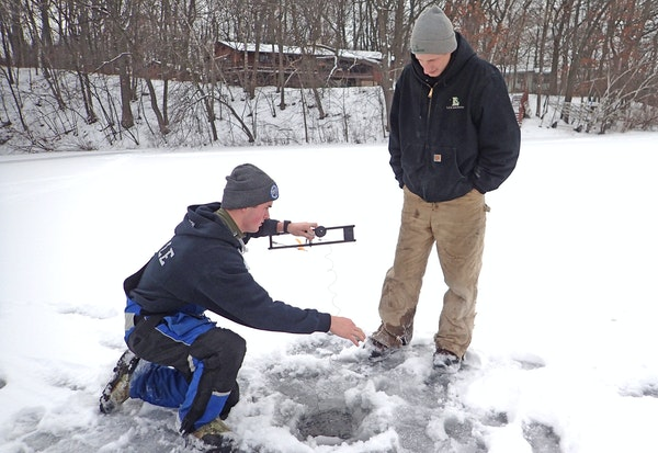 Jake Erickson, left, of Oakdale checked a tip-up, hoping a northern pike would be hooked, while Justin Meyer of Maplewood watched. They were fishing o